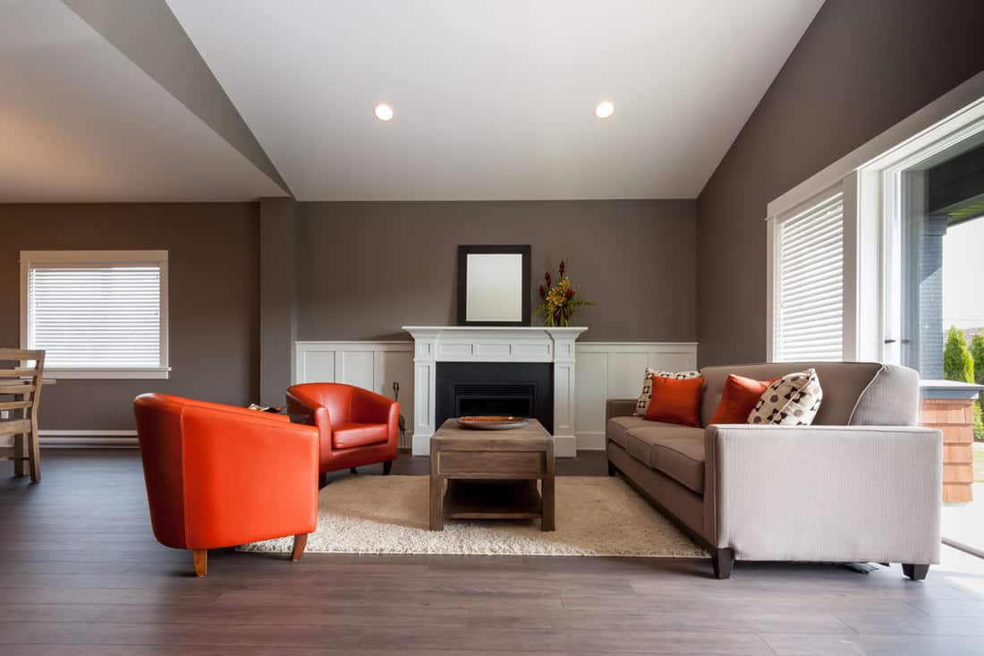 Brown living room with gray flooring and long couches