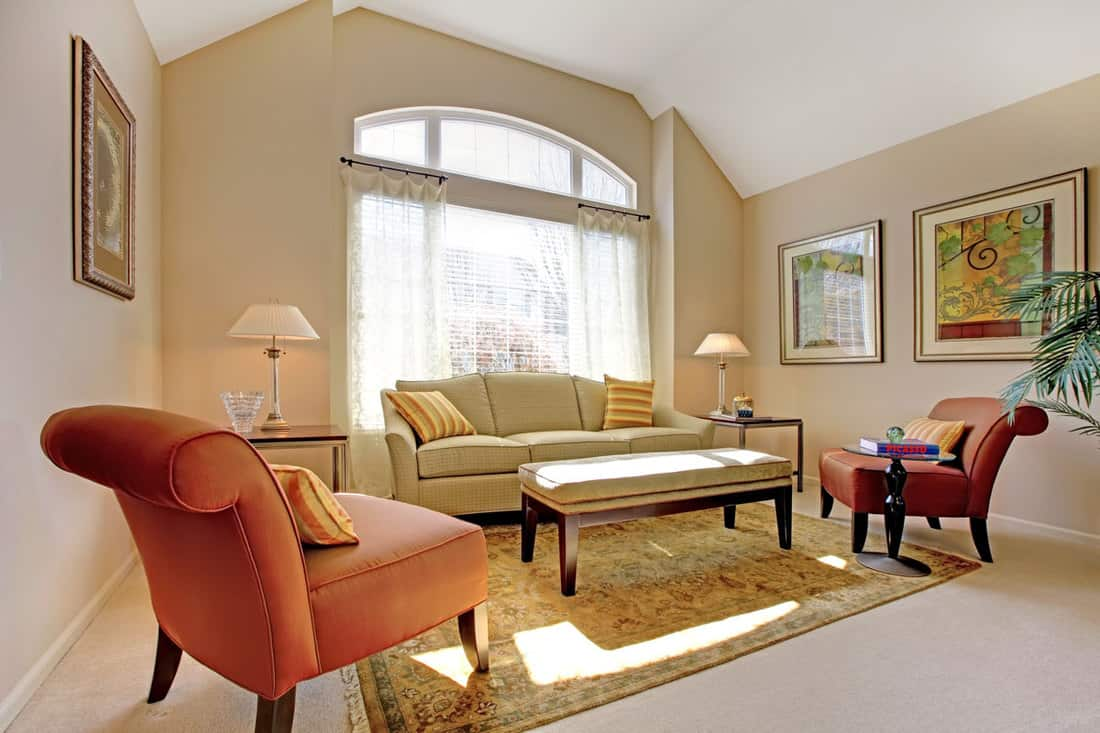 Brown walled living room with orange and white chairs complementing living room