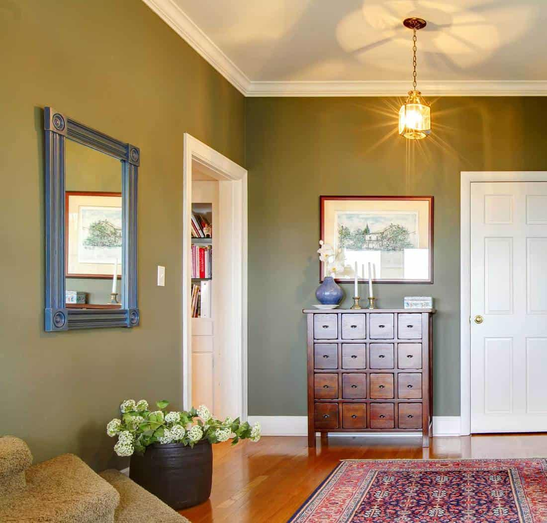 Classic hallway with green walls, flowers and rug