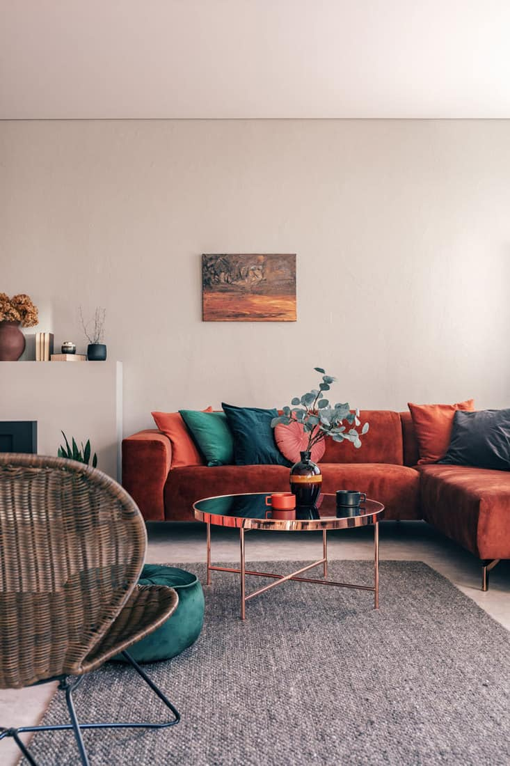 Colorful couch pillows and light brown colored walls in the background