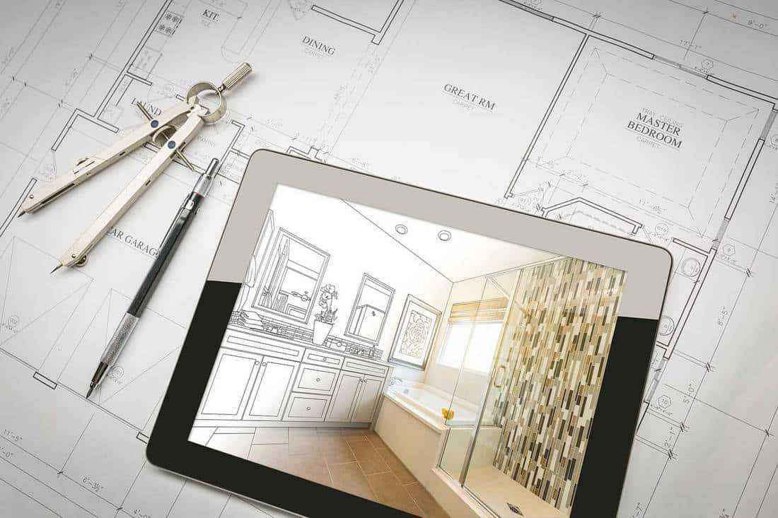 Computer tablet with master bathroom design over house plans, pencil and compass