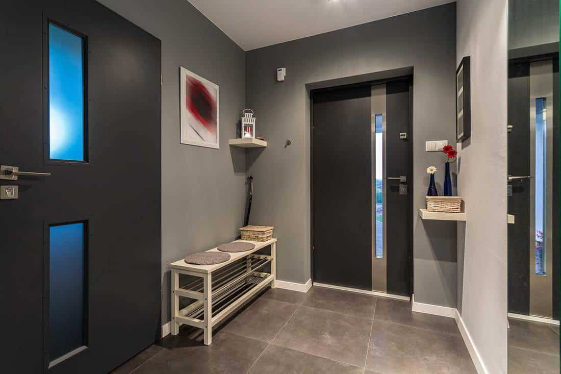 Cosy hall with black doors, gray walls, framed wall art decor and entryway shoe rack