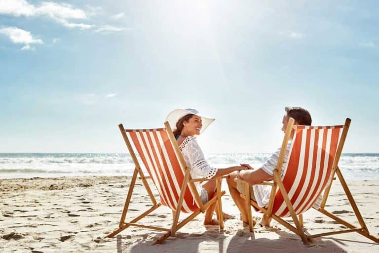 Couples enjoying a day at the beach while sitting on beach chairs, Where To Buy Beach Chairs