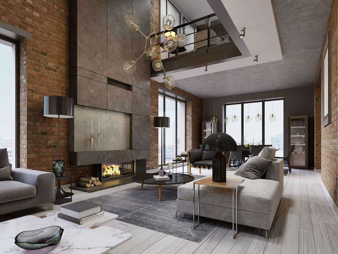 Cozy gray sofa, magazine table and large designer fireplace in a loft-style apartment living room