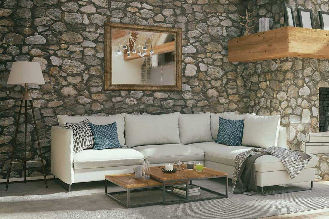 Cozy living room with stone walls, large mirror and sofa