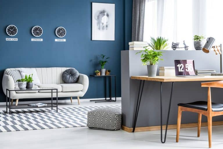 Dark blue living room interior with three clocks, simple poster, bright sofa and home office corner with laptop on hairpin desk, Study Area in Living Room: 17 Photo Examples