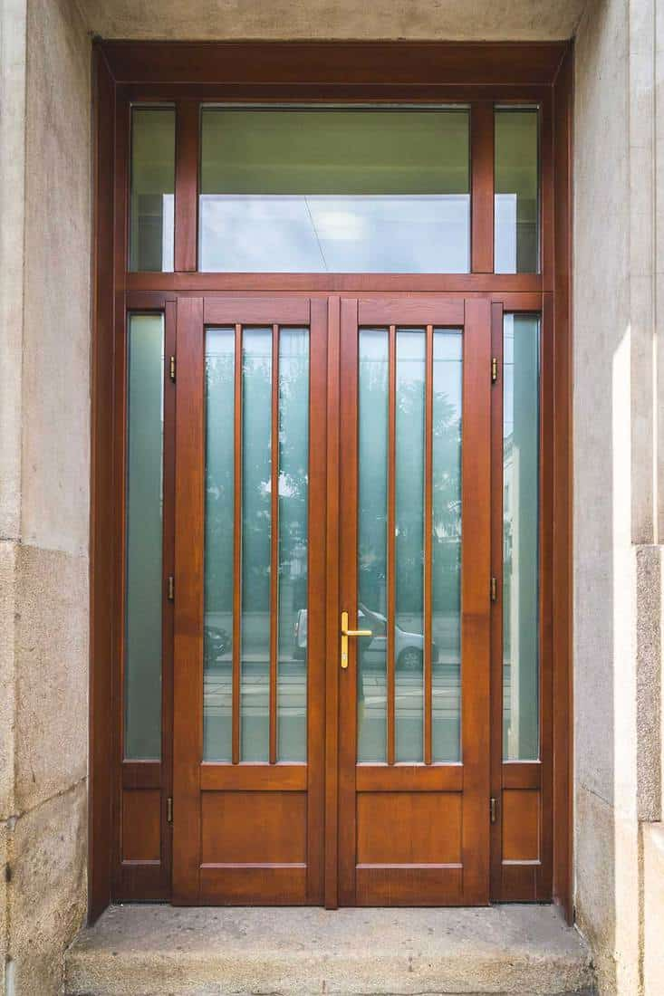 Elegant brown wooden double door entrance with transparent glass