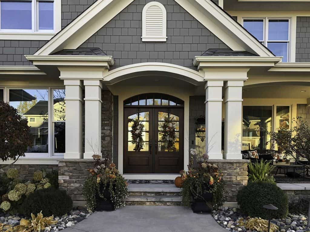 Entrance of a modern home with decorations on front brown double door