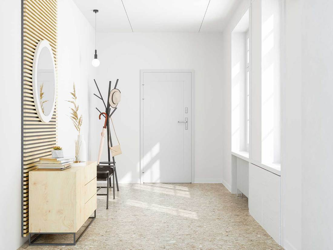 Front door entrance to house with tiled floor, white walls and round mirror