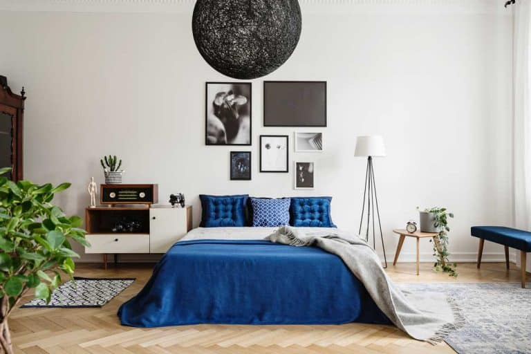 Gallery of framed art on white wall and black chandelier in navy blue bedroom in tenement house, How to Decorate Your Bedroom Walls [3 Questions to Ask Yourself]