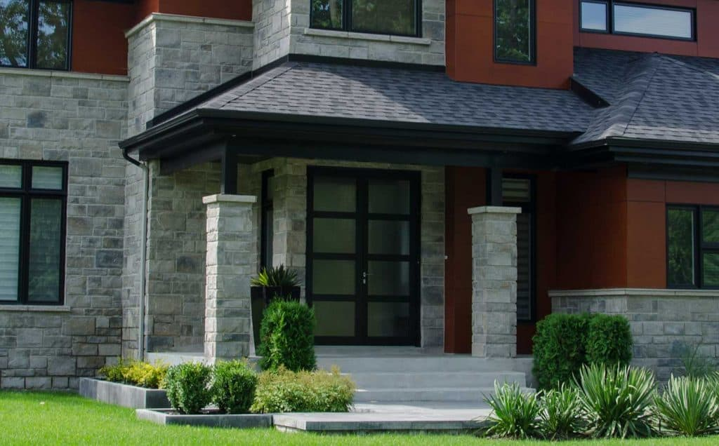 Glass double door entrance of a modern luxury home with stone brick walls