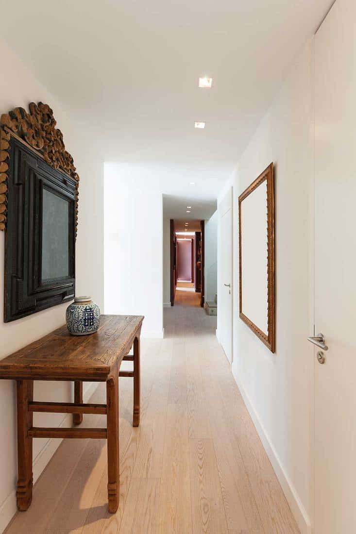 Hallway corridor of a modern apartment with framed decoration, mirror and console table