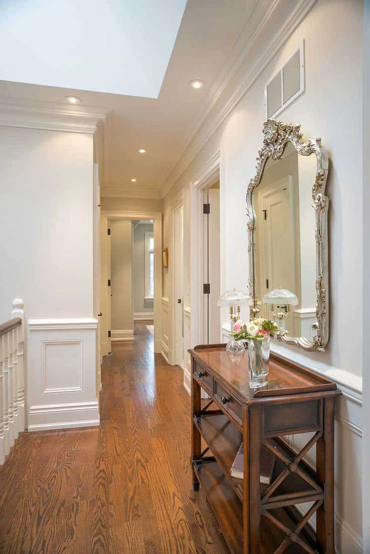 Hallway interior of a brand new custom home residence with antique mirror and console table