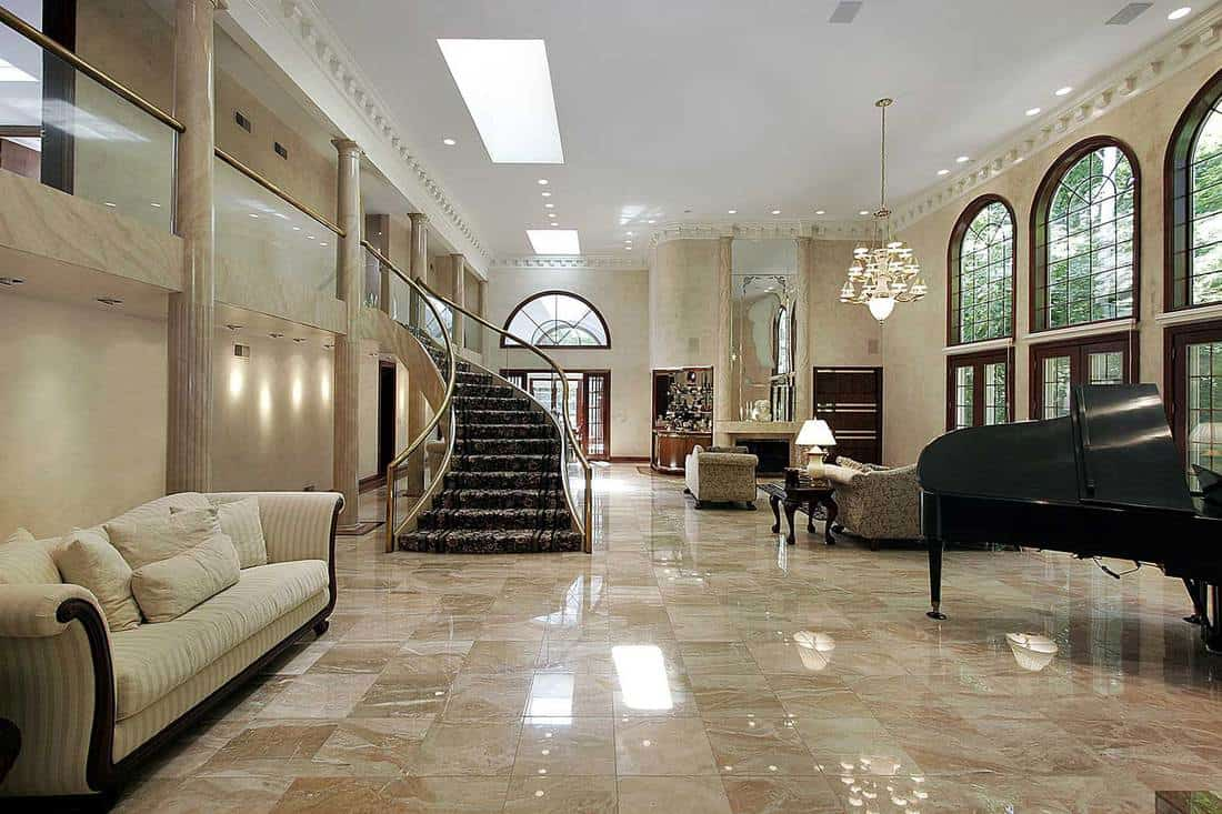 Huge great living room interior with marble floors, grand piano and staircase