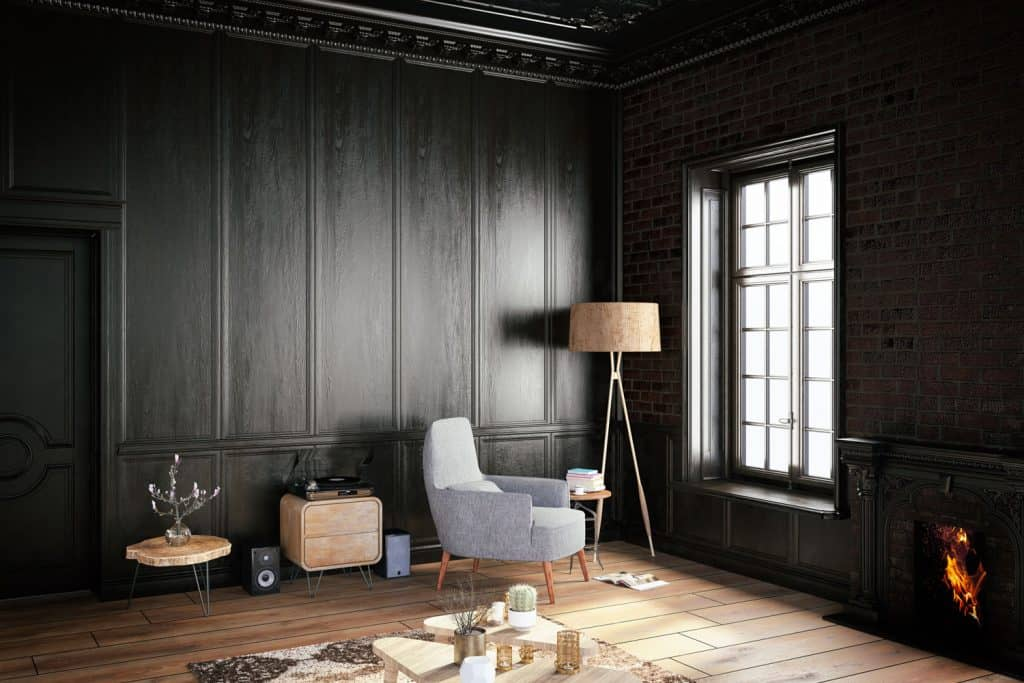 Interior of a dark themed living room with dark flat panel wall, wooden laminated flooring, and a fireplace on the right side