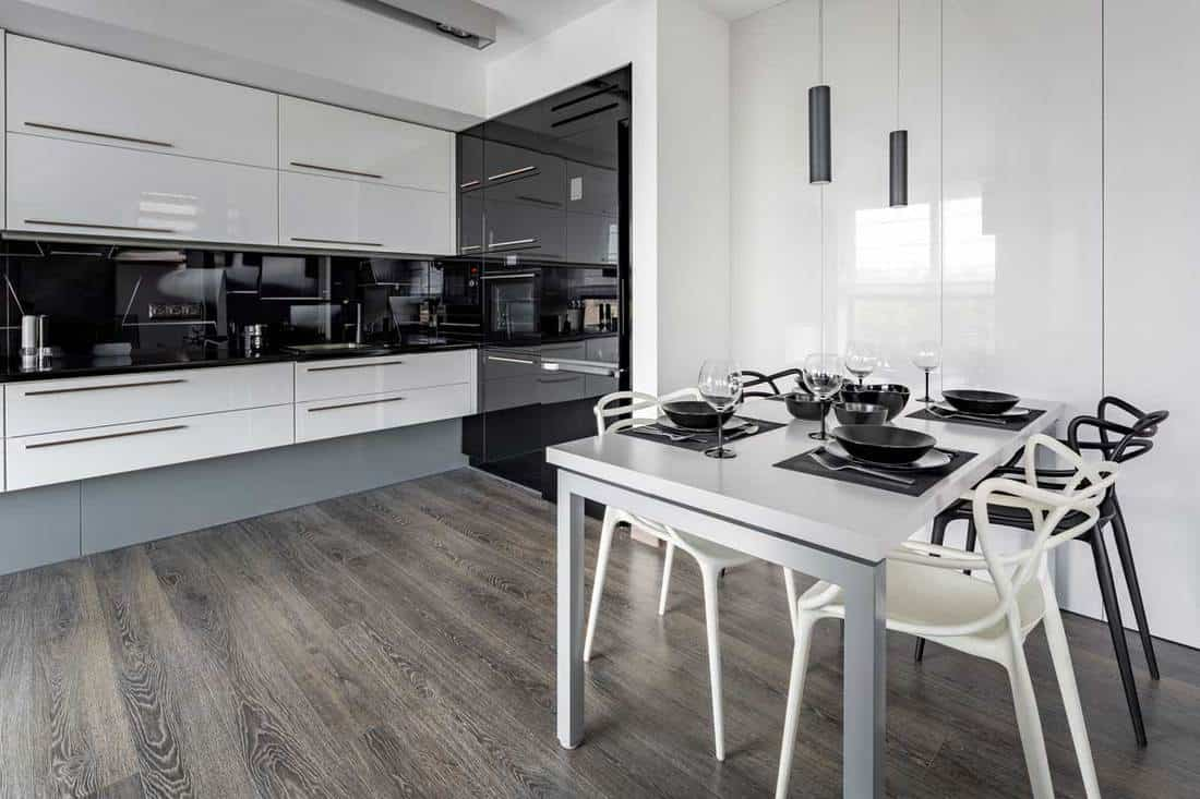 Kitchen with white table, black wall tiles and new design chairs