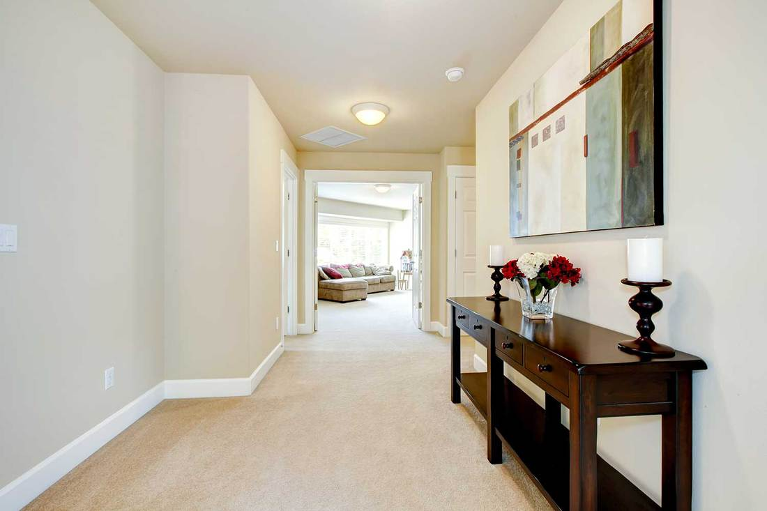 Large home hallway with beige carpet, art and furniture