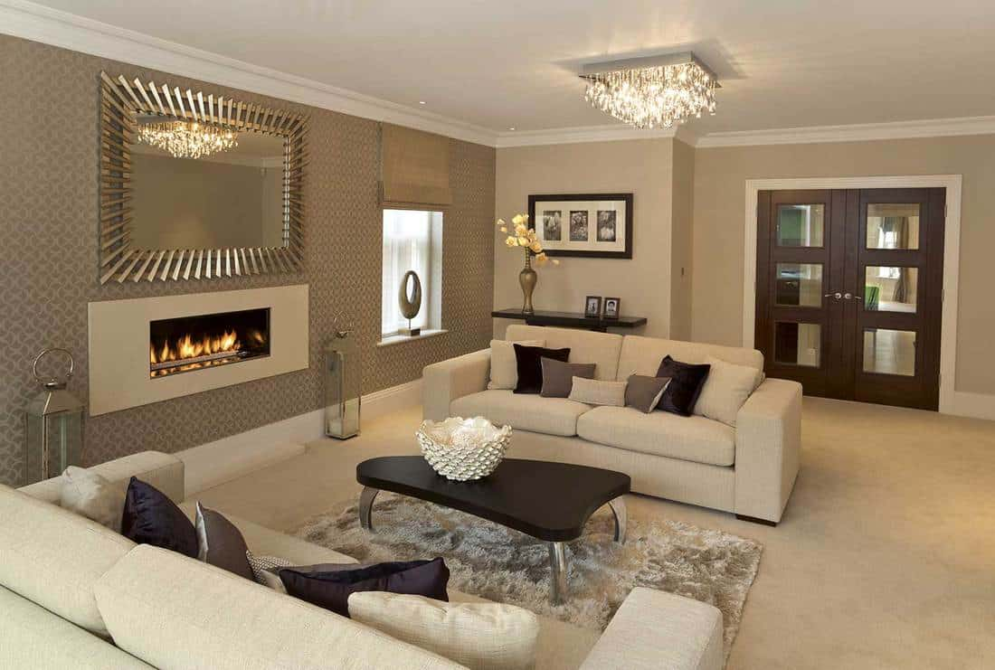 Large living room in a new house with two large settees covered with silk cushion seats alongside a beautiful modern gas fireplace