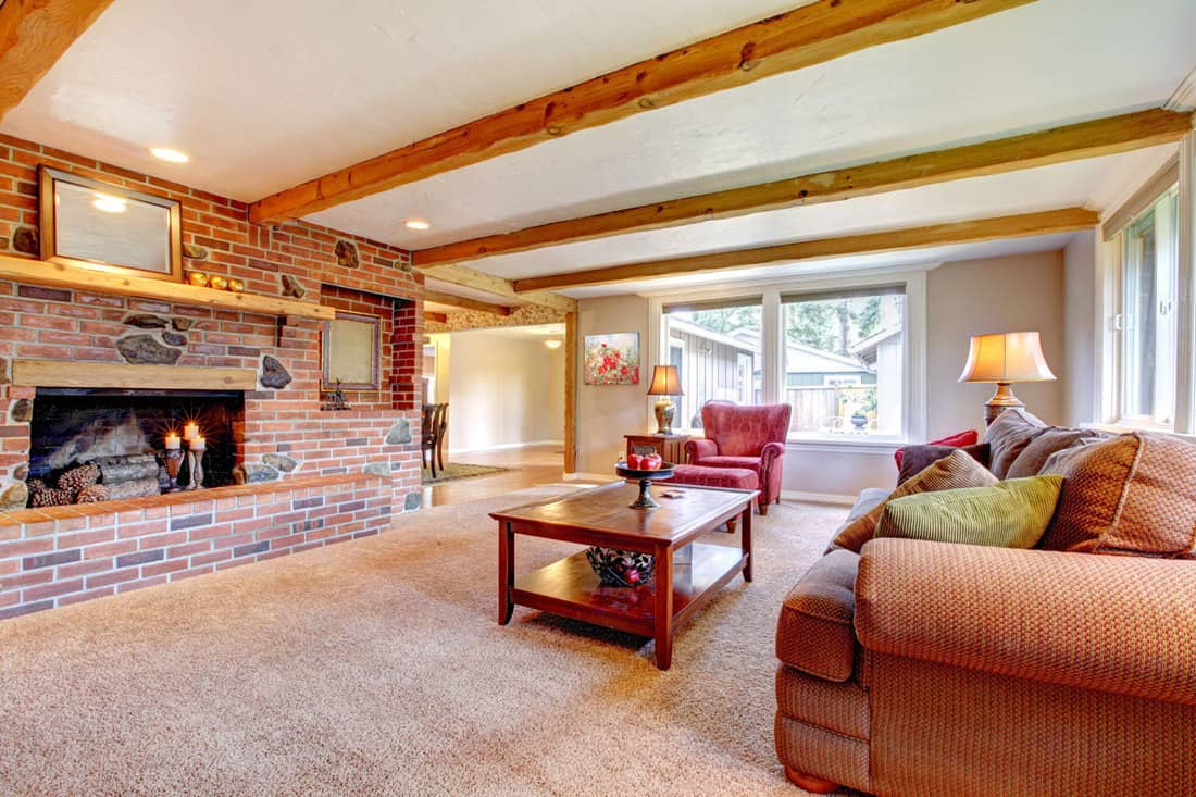 Large living room with fireplace decorated with brick wall and white ceiling with wooden trusses