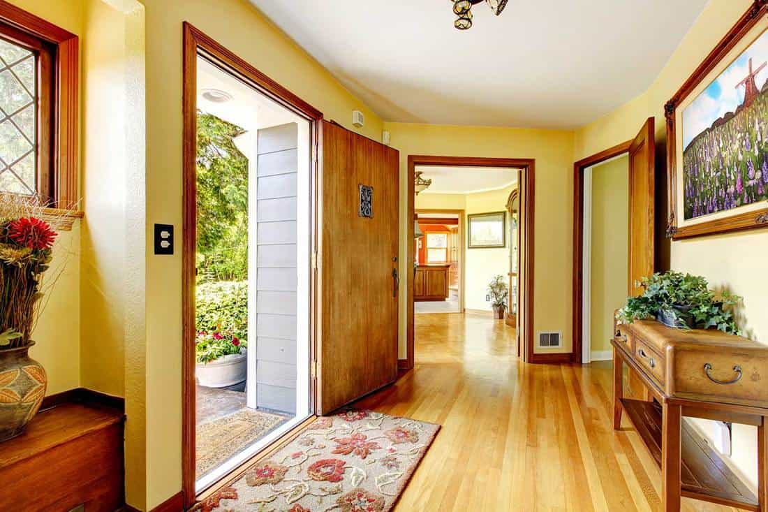 Large old luxury house entrance interior with art and yellow walls