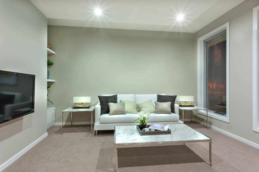 Light gray colored walls with white couch and TV mounted at wall