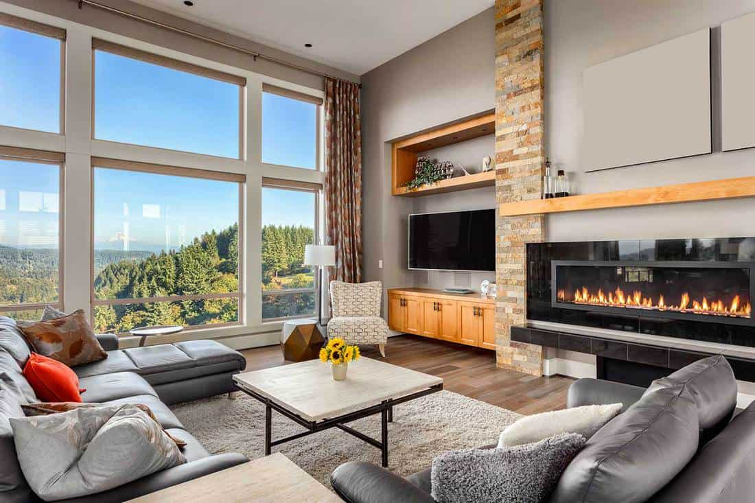 Living room in luxury home with gray sofa, fireplace and amazing mountain view