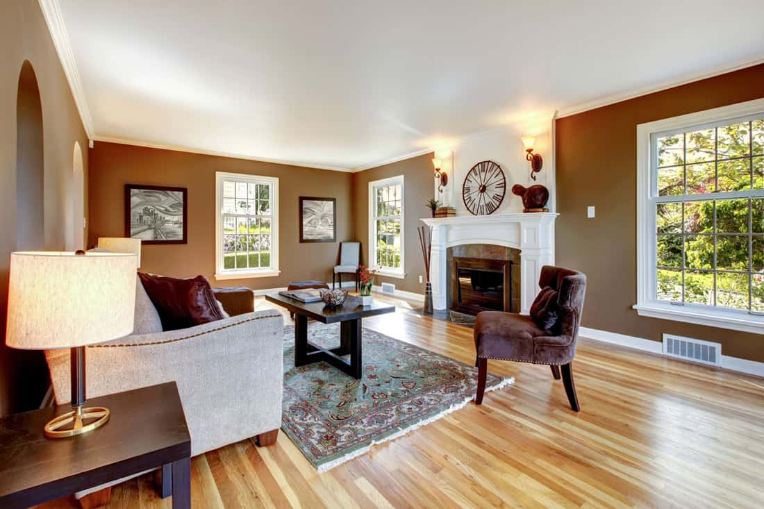Living room with brown walls wooden flooring and center fireplace