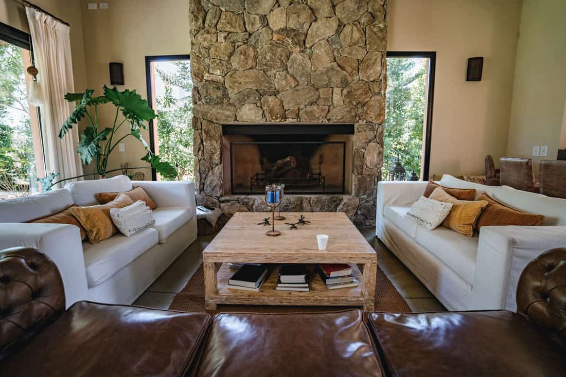 Living room with decorative rock paneling fireplace and white couches