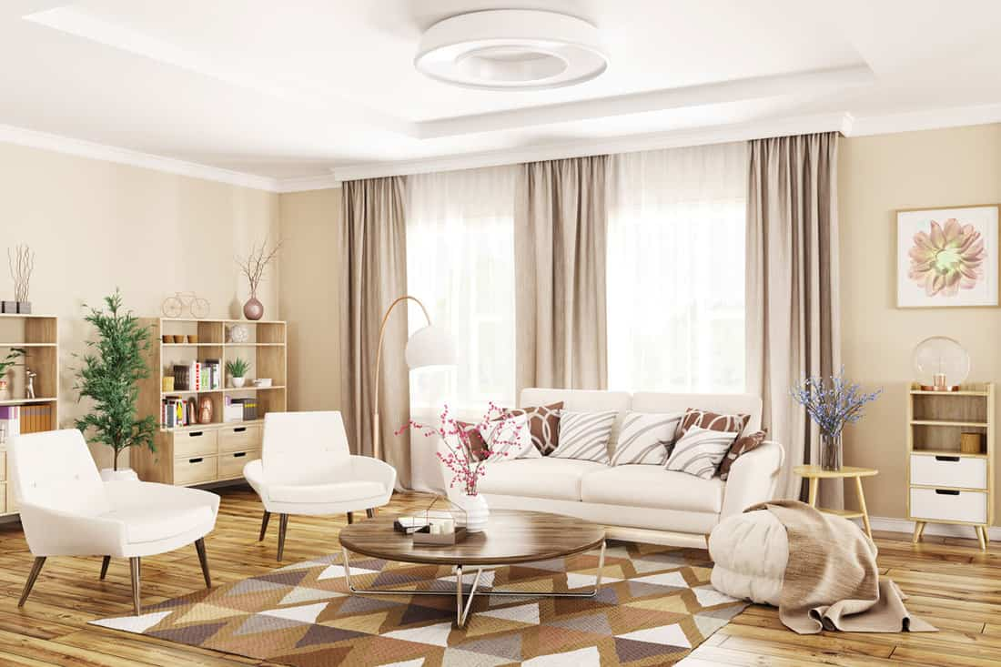 Living room with triangle patterned rug and white sofas with pillows and cream colored curtains