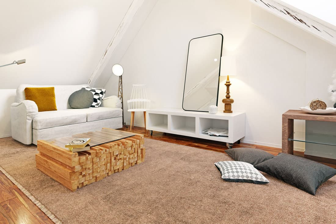 Living room with white colored walls and huge rug on floor and white solid wooden table