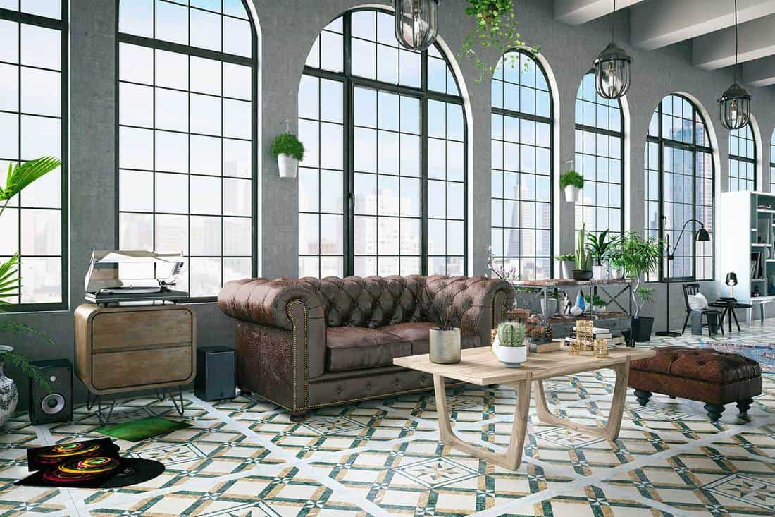 Loft house interior with industrial lighting, house plants, rustic sofa and wooden coffee table