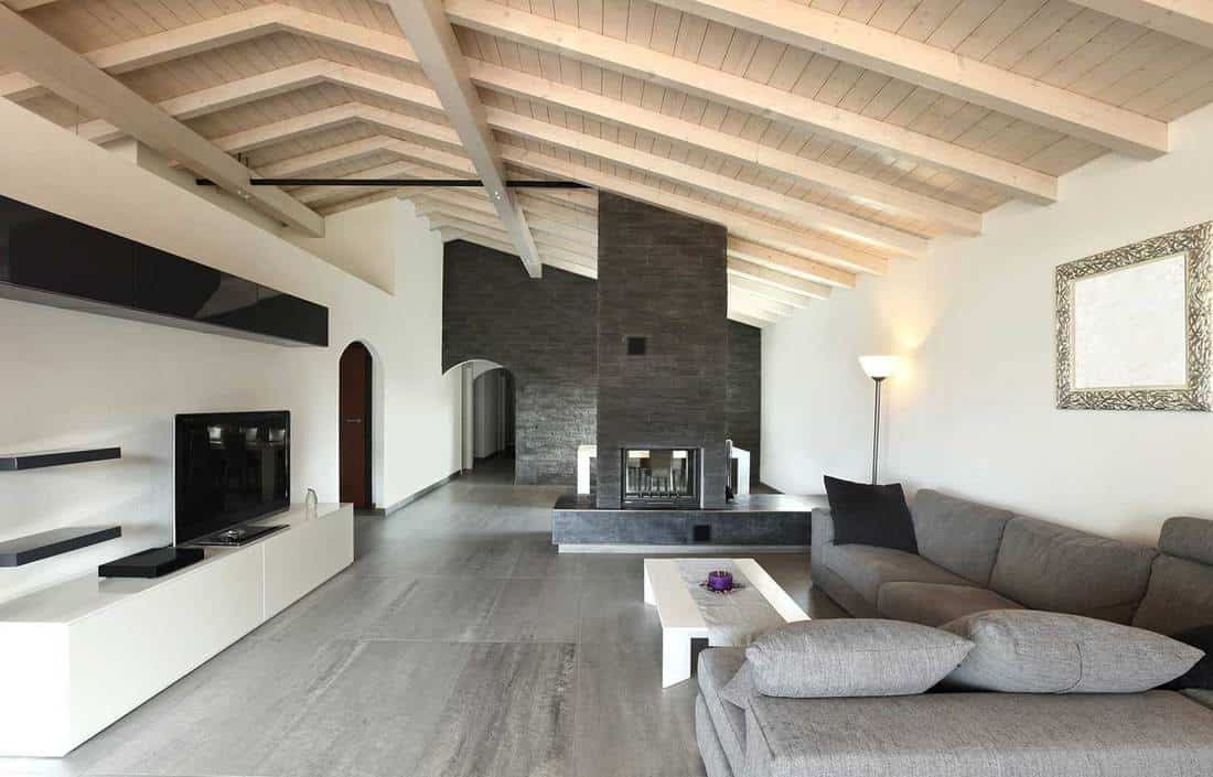 Luxury large attic living room interior with cozy sofa, tv, and fireplace