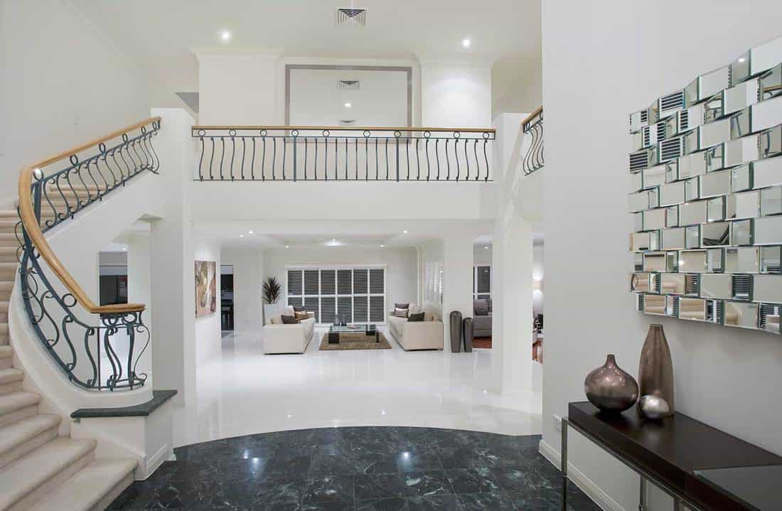 Luxury mansion entrance with marble floor and decorative mirror