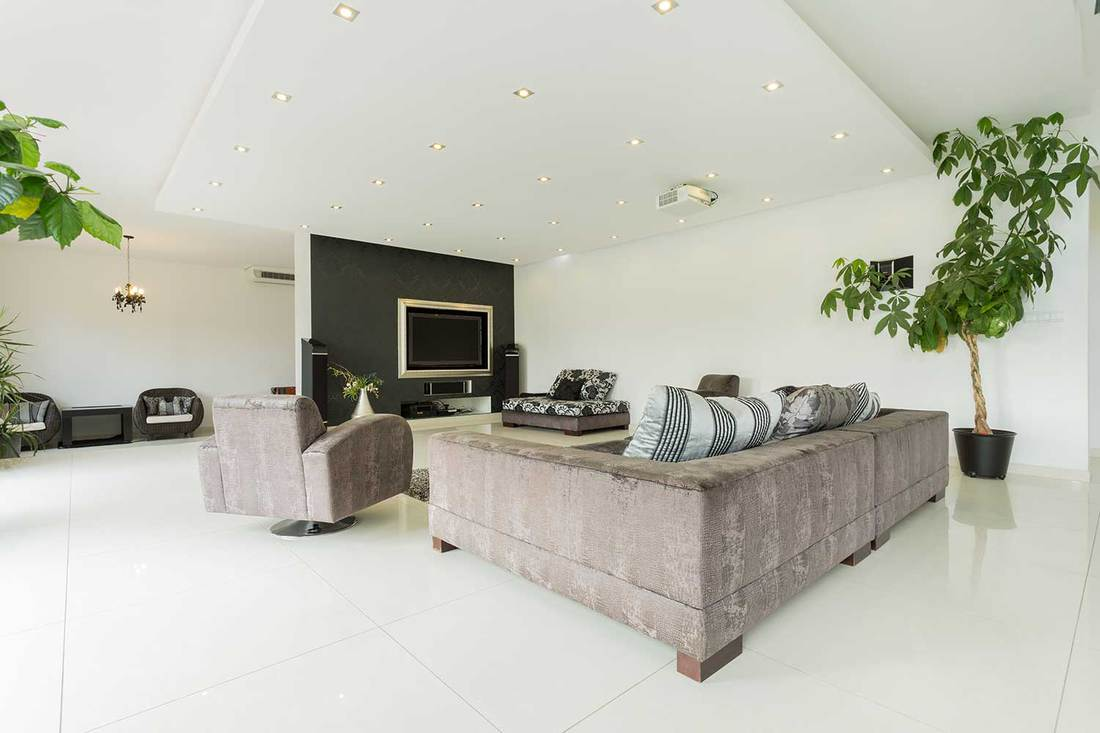 Luxury mansion living room interior with gray sofa, white tiled floors and widescreen tv