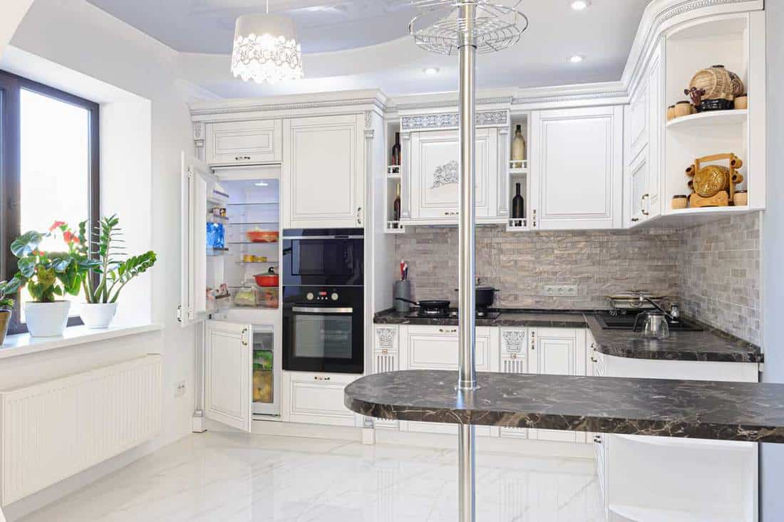 Luxury modern white colored kitchen in modern Provence style. Some drawers and doors are open