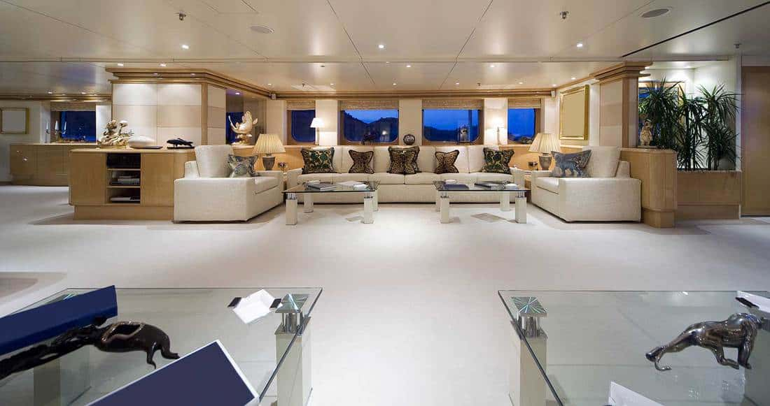 Main lounge of a super yacht with white sofa set and throw pillows