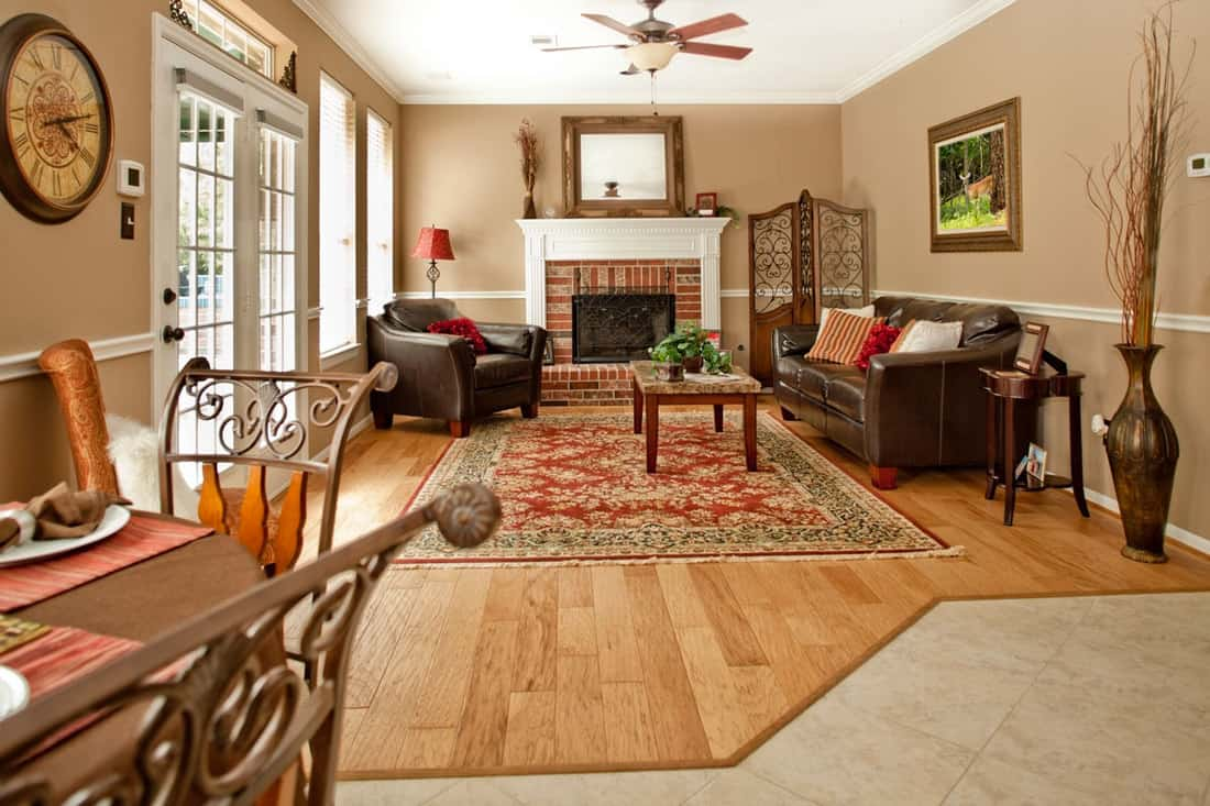 Mediterranean living room with brown sofa and fireplace at center