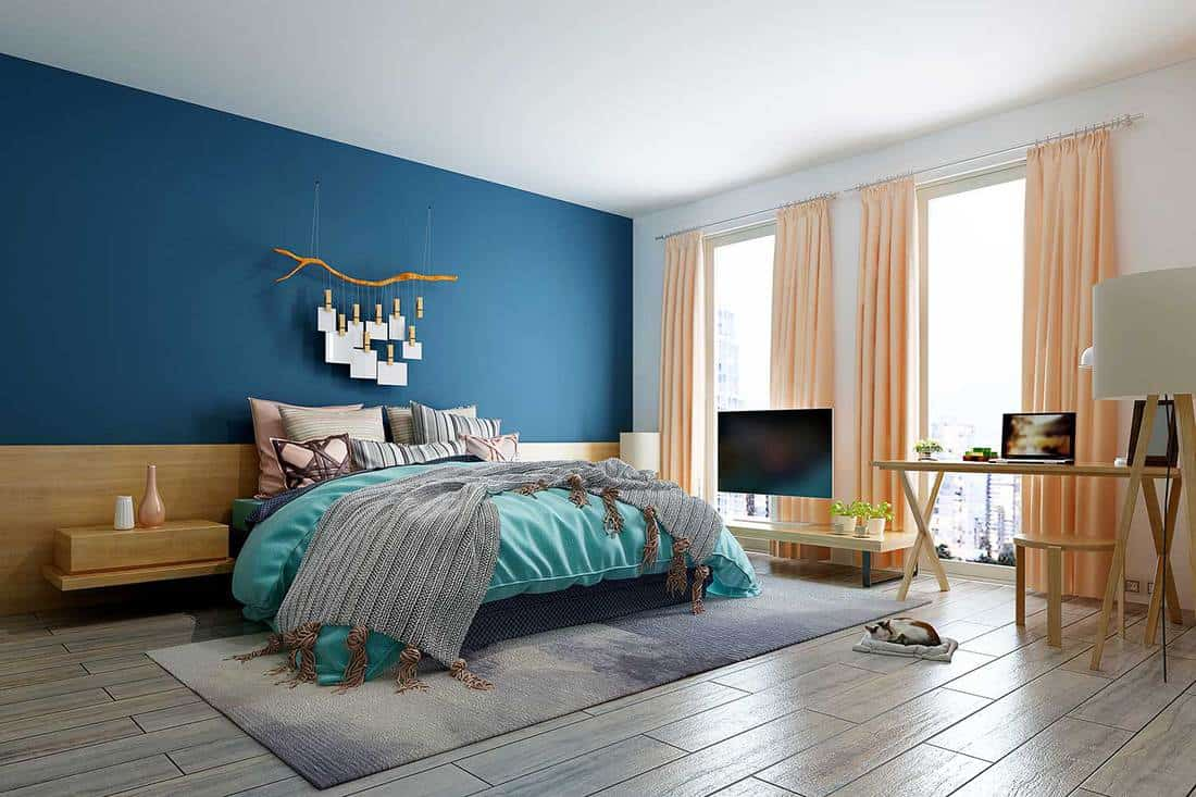Modern bedroom of a condo house with blue wall, parquet floor, teal duvet cover and view of the city