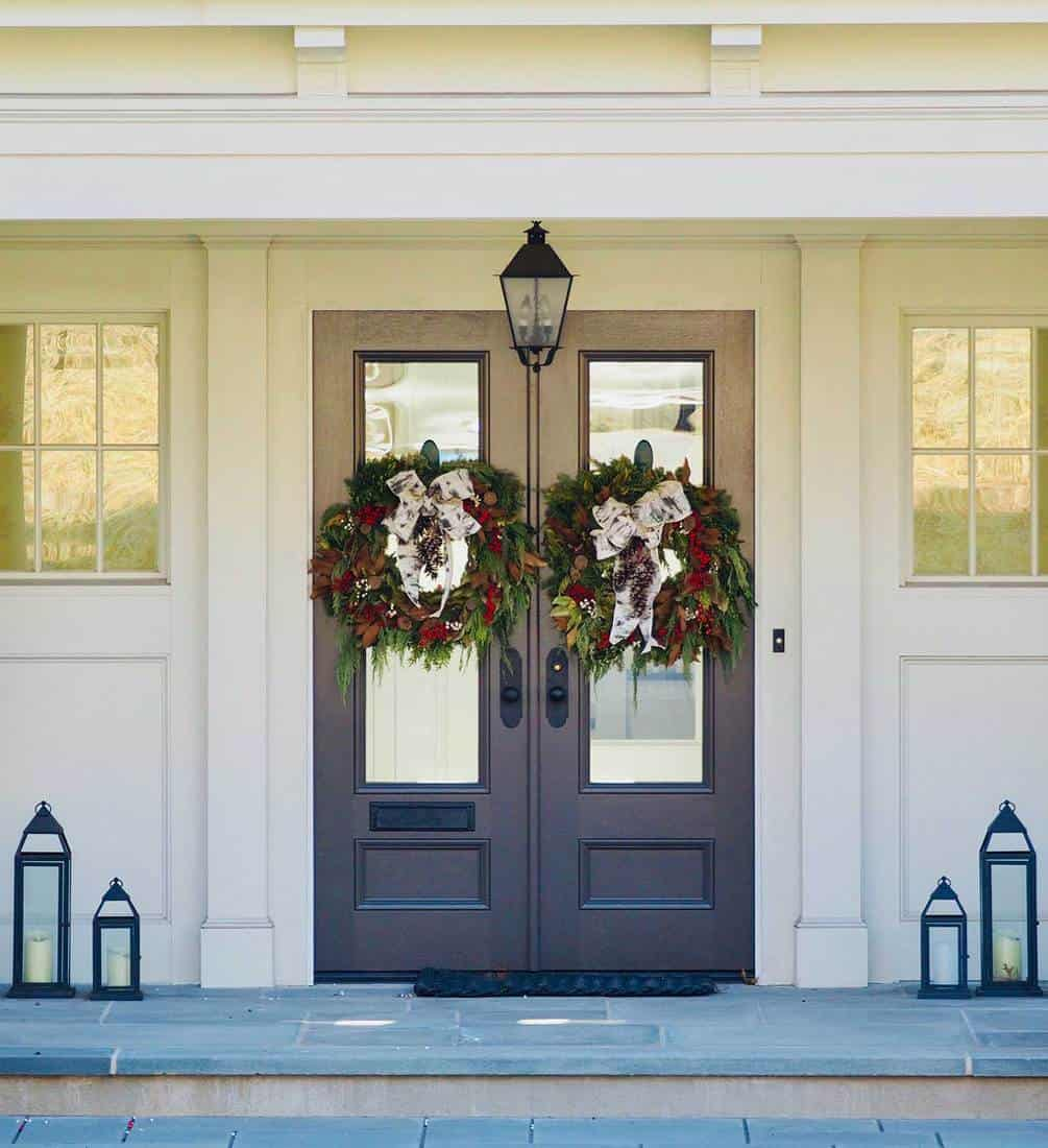 Modern black double doors on New Jersey home decorated with Christmas wreaths