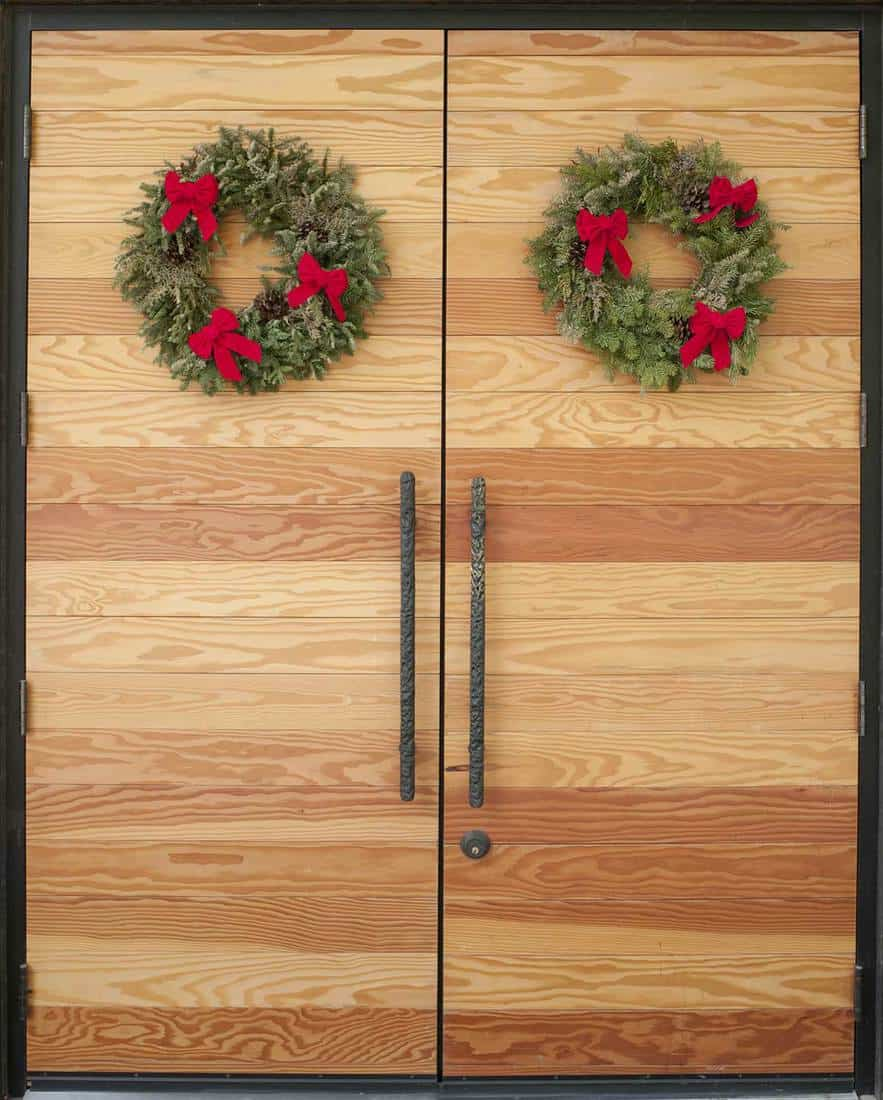 Modern double door decorated with Christmas wreaths