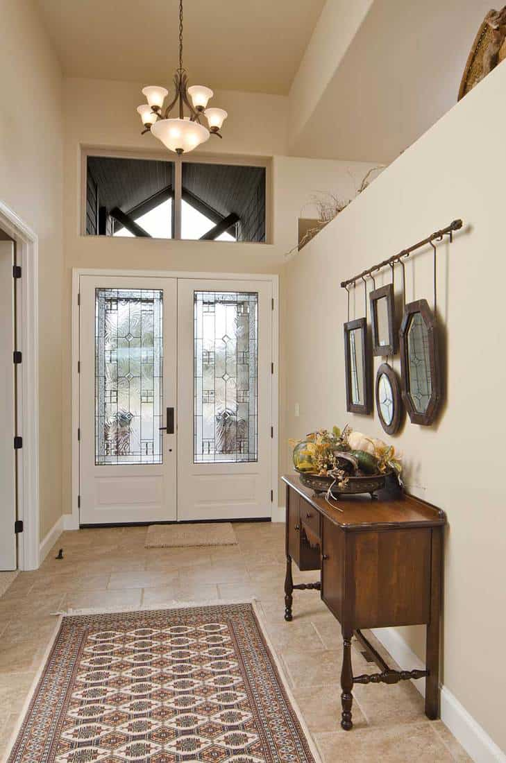 Modern hallway with white glass double door, decorative mirror and console table