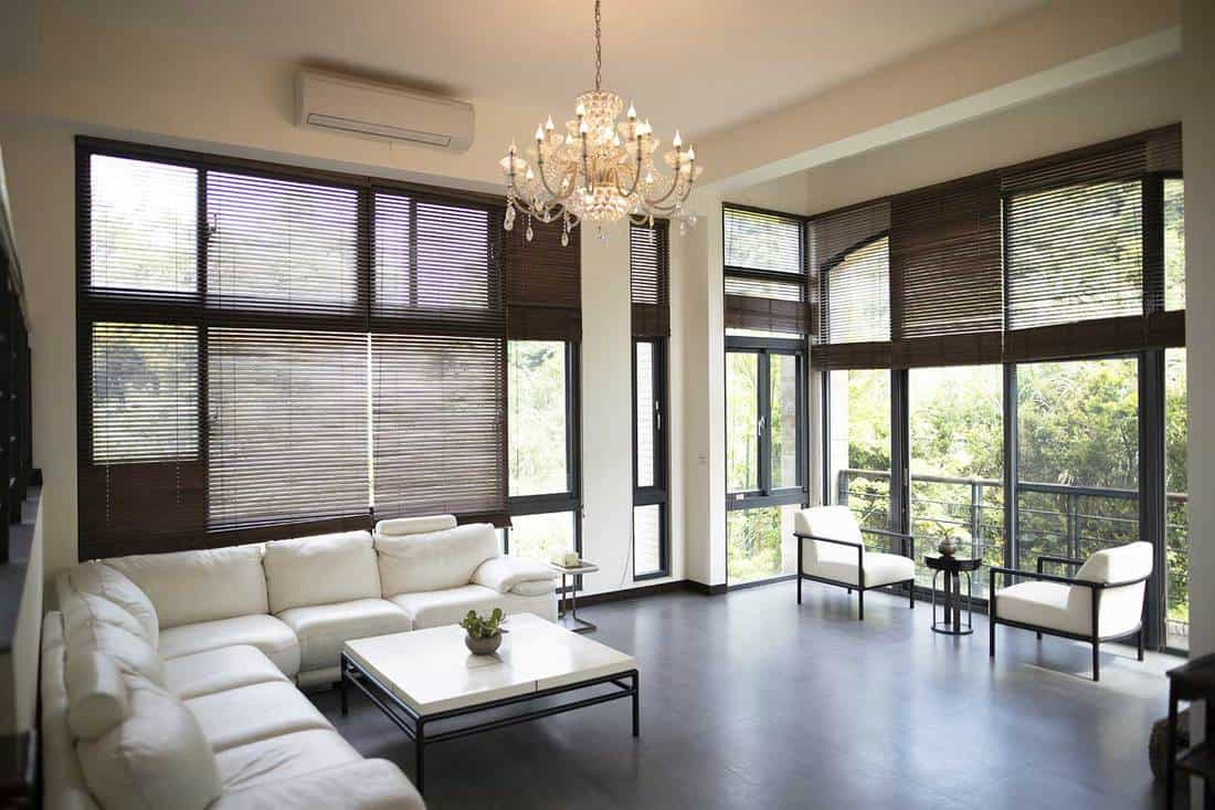 Modern house living room interior with chandelier, white corner sofa, accent chairs and coffee table