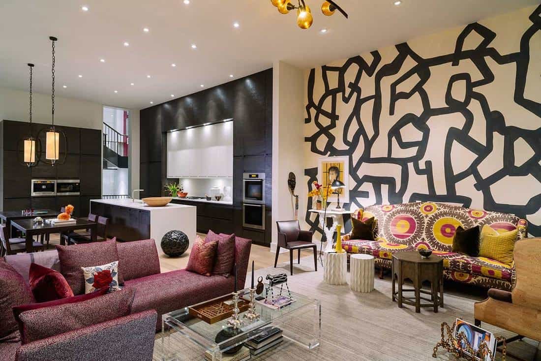 Modern interior of newly designed and constructed luxury condo apartment with color coordinated furniture and fabrics, art work on the wall and around the world souvenirs