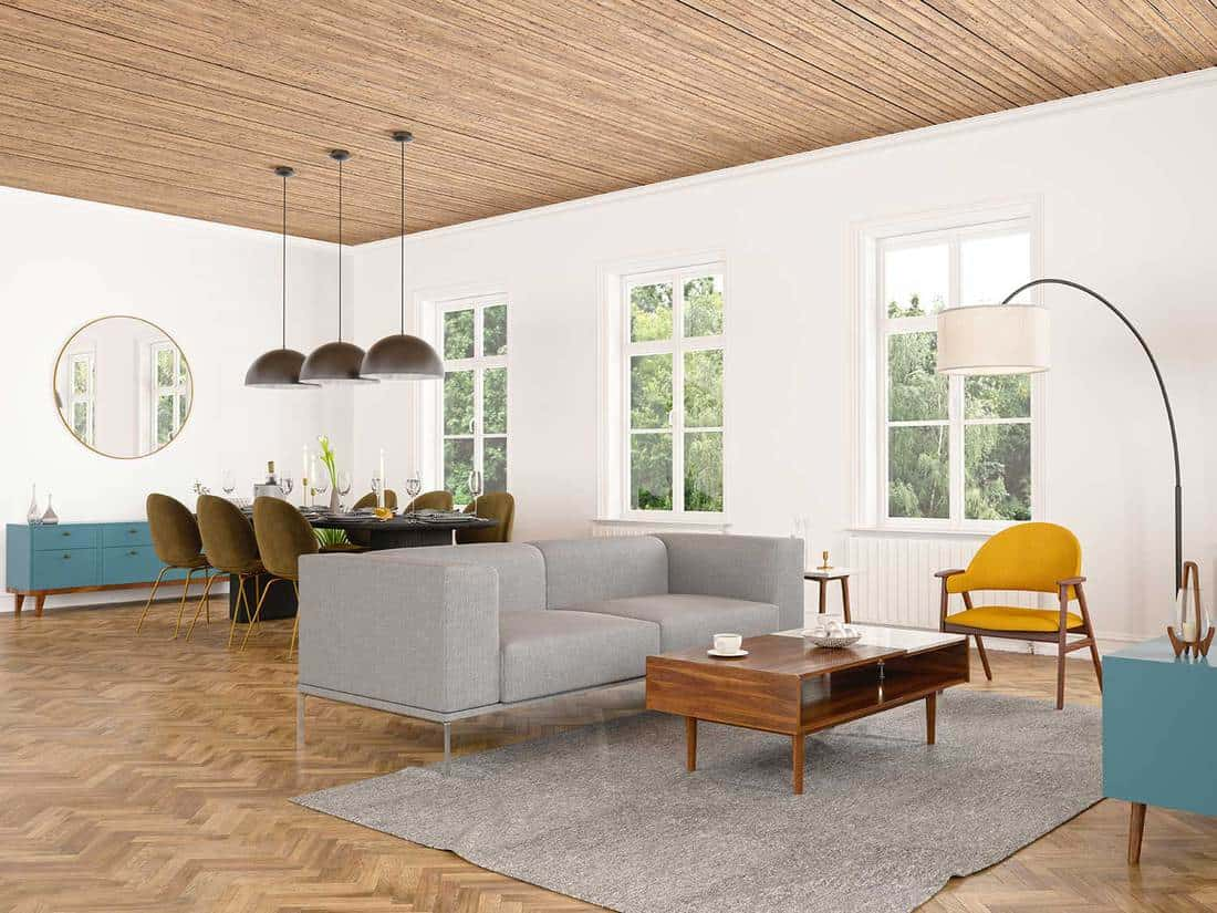 Modern living room and dining room interior with gray sofa, coffee table and parquet floor