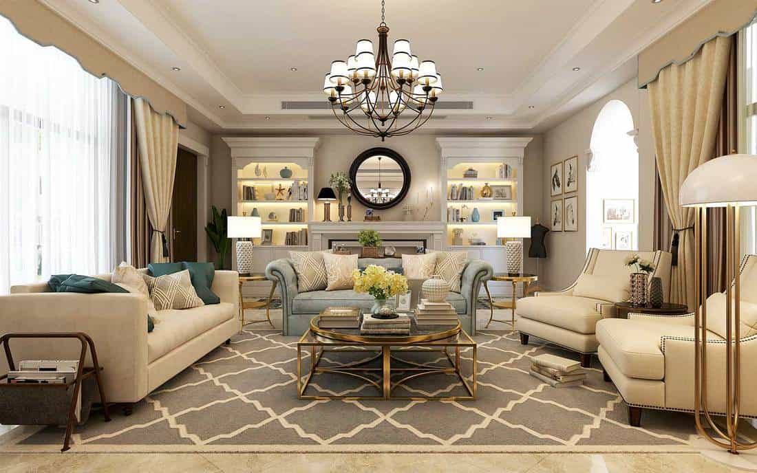 Modern living room interior with beige and gray sofa, chandelier, round mirror and gold center table
