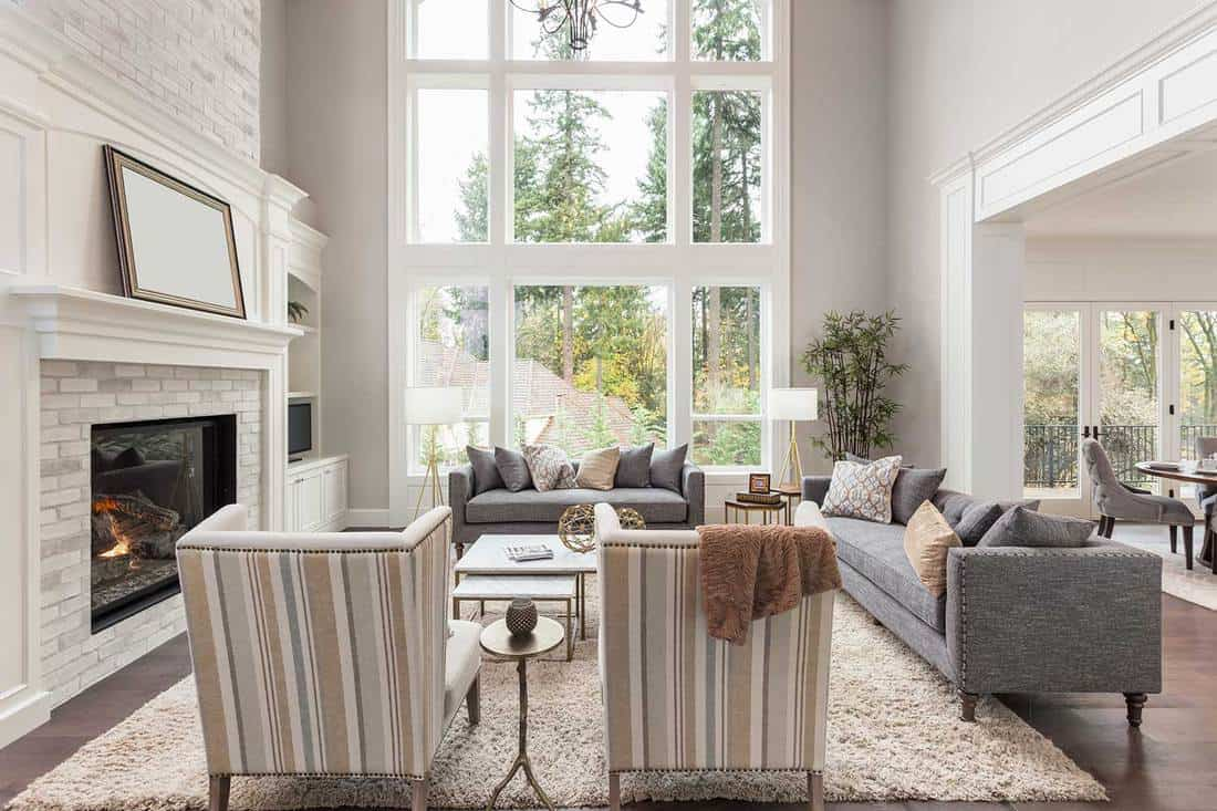 Modern living room interior with tall vaulted ceiling, hardwood floors, gray sofa, accent chairs, mirror and fireplace in newly constructed luxury home