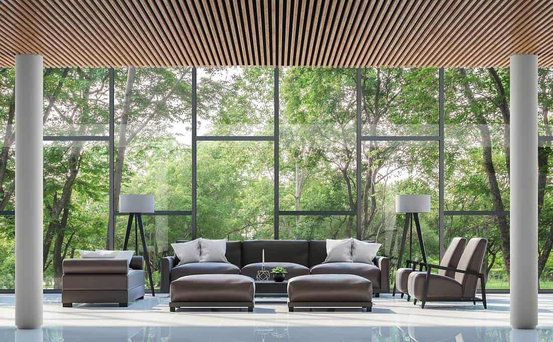 Modern living room interior with white tiled floor, wood lattice ceiling and large window overlooking the surrounding garden and nature