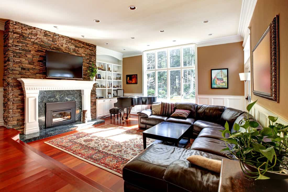 Modern living room with wooden flooring, curved couch, and brown walls with fireplace