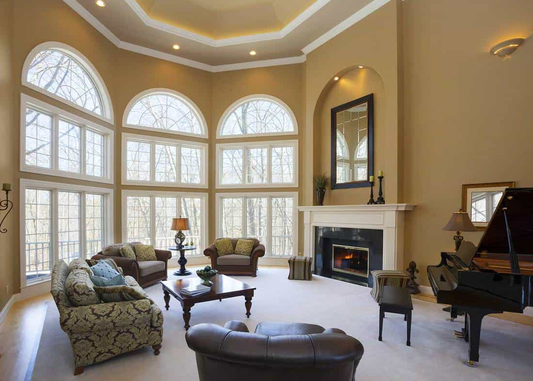 Modern luxury living room with vaulted ceiling, fireplace and a grand piano