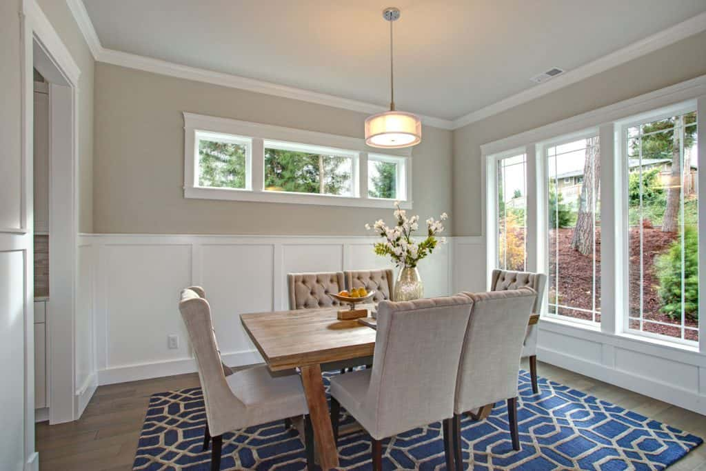 Modern Victorian themed dining area with gray painted walls and a board and batten wall